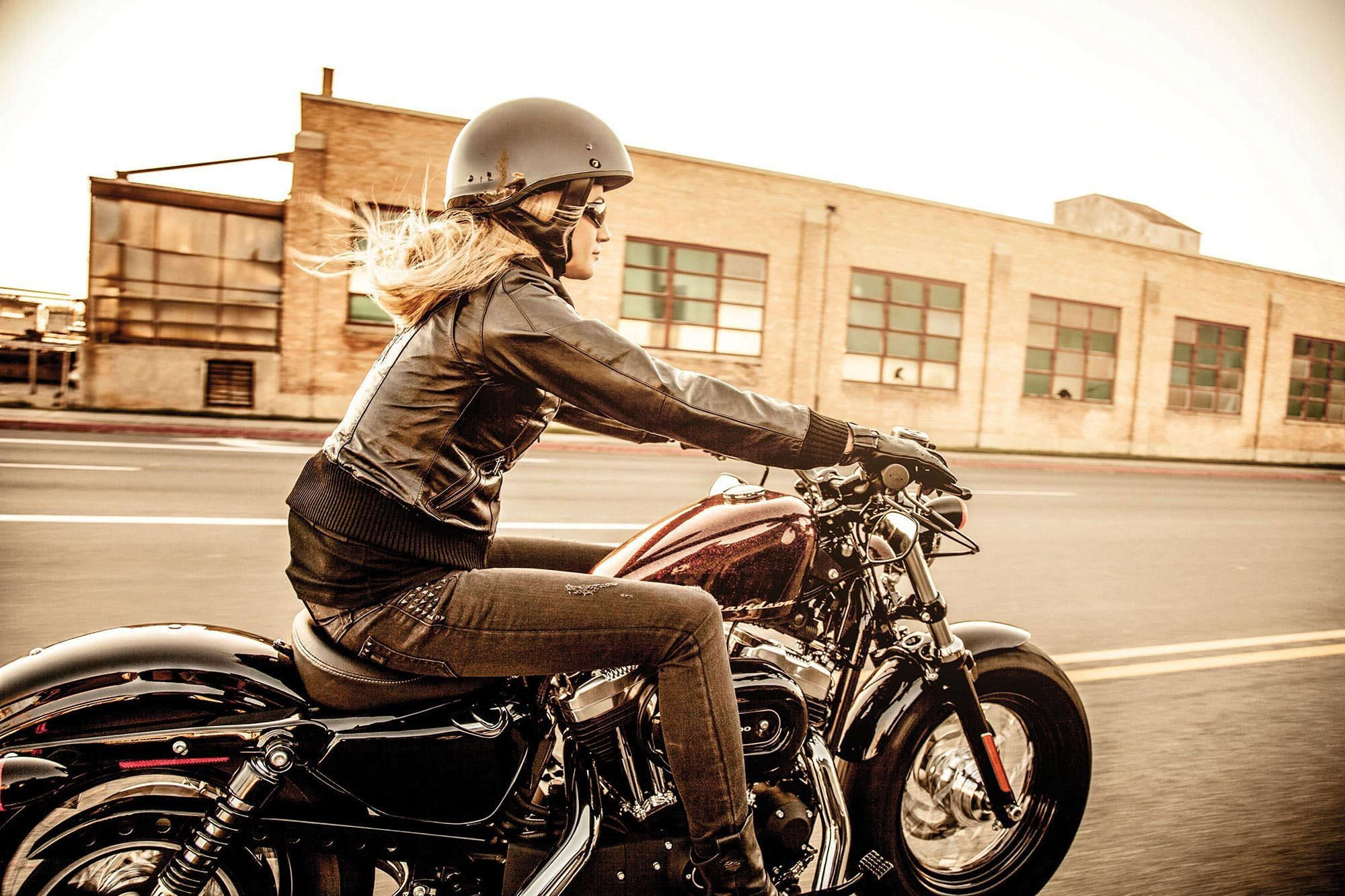 Woman riding Harley Davidson Motorcycle in Industrial Area