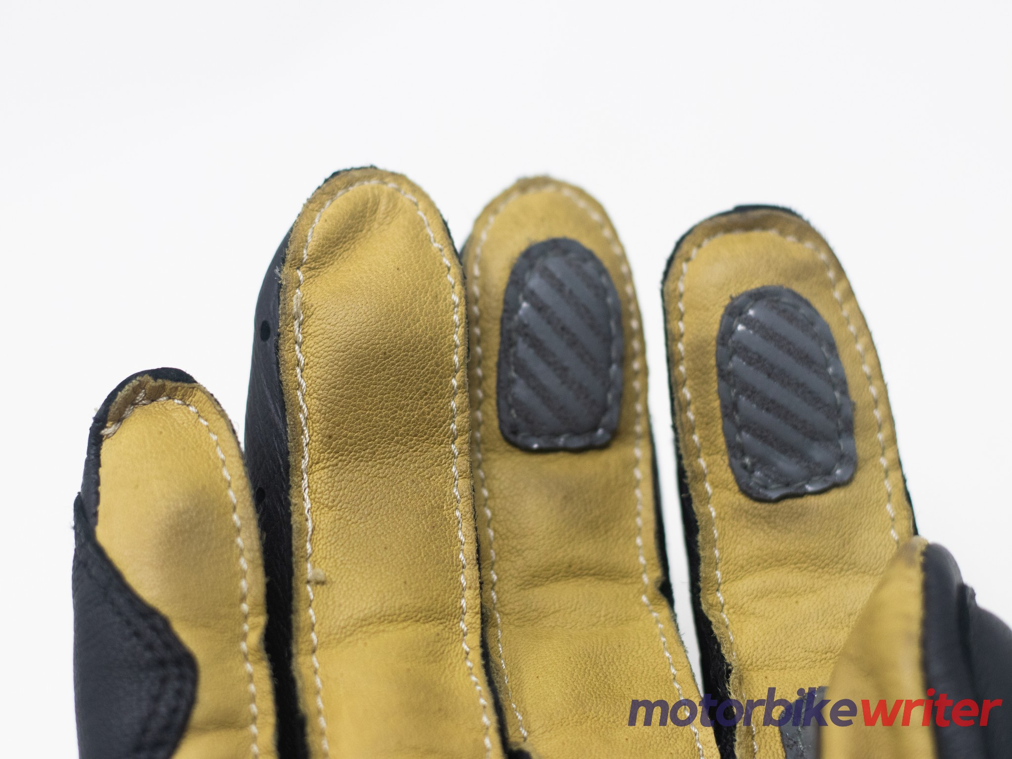 Grip pads stitched onto the fingertips of leather palm glove