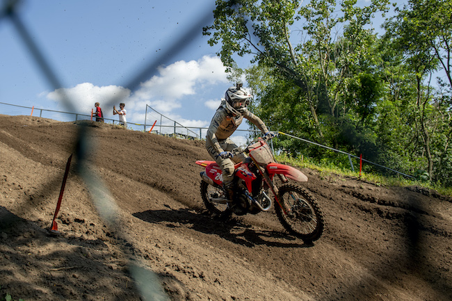 A racer from Team HRC racing down a dirt hill at the MXGP Championship