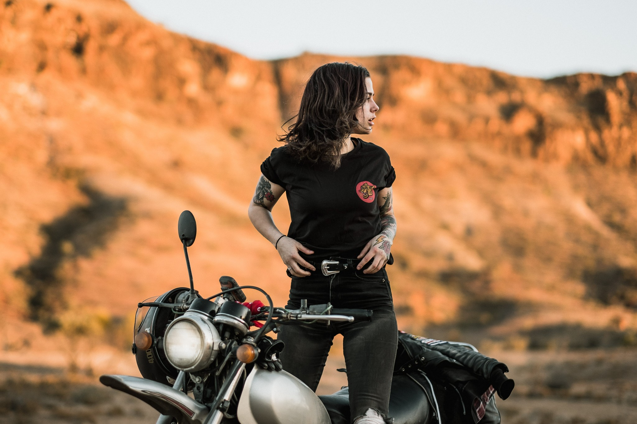 Woman on a motorcycle at dusk in a Tasmanian field