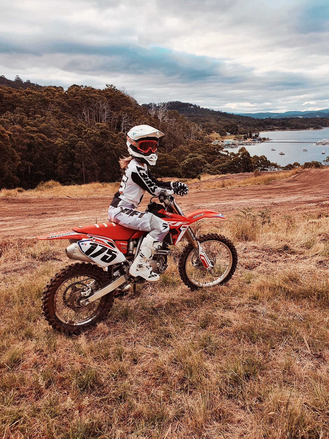 Woman on a motocross motorcycle at dusk in a Tasmanian field