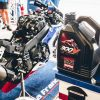 A View of the Motul 300V Factory Line Racing Kit Oil 2376H 0W-30 ESTER Core® next to a Honda Racebike
