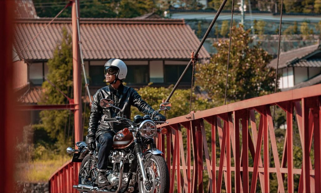 a rider enjoying the 2022 Kawasaki W800 on a red bridge