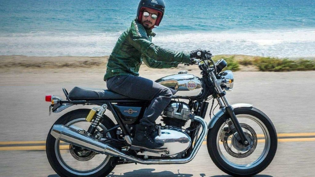 A man trying out a Royal Enfield motorcycle, wearing a Royal Enfield helmet